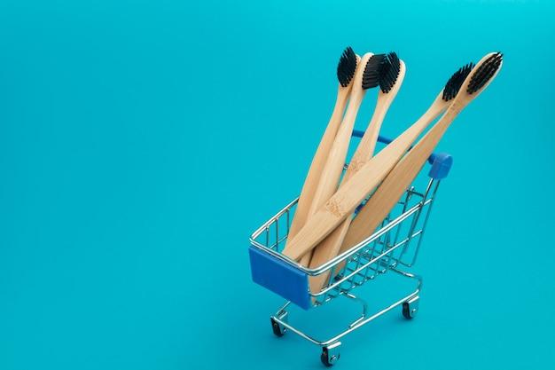 Escova de dentes de madeira no carrinho de compras sobre fundo azul
