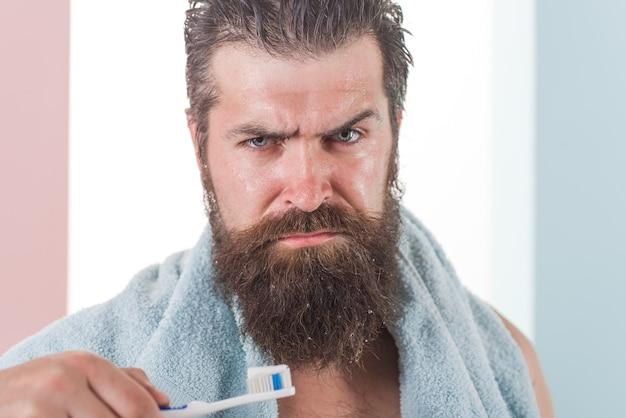 Escova de dentes de rotina matinal de cuidados dentários homem barbudo com escova de dentes escovando os dentes limpando os dentes