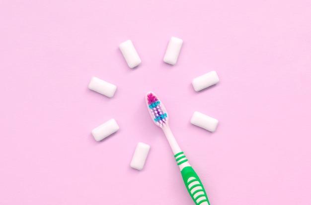 Escova de dentes e chicletes de mentira em um rosa pastel