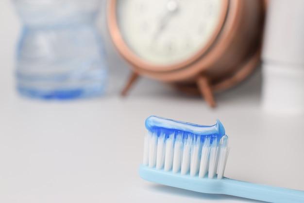 Escova de dentes e creme dental no fundo desfocado, closeup