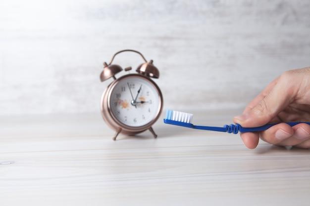 Escova de dentes e despertador na hora de escovar os dentes