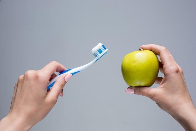 Escova de dentes e maçã nas mãos da mulher em cinza