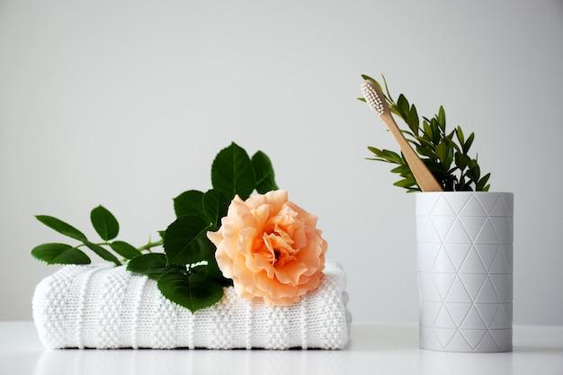 Escova de dentes ecológica de madeira em suporte branco com rosa laranja e toalha branca