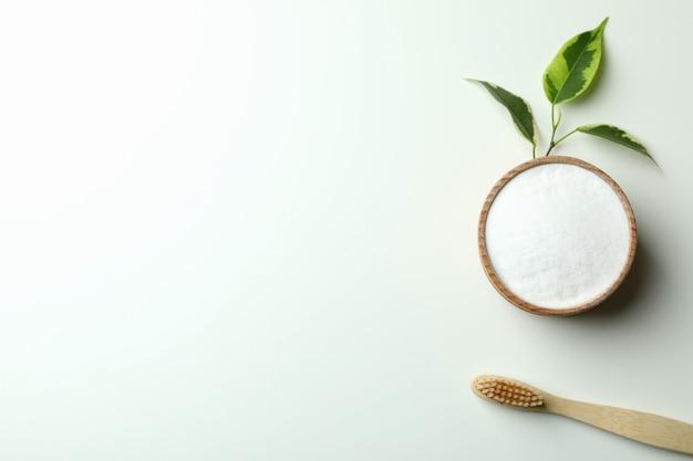 Escova de dentes ecológica e pó dentário em fundo branco
