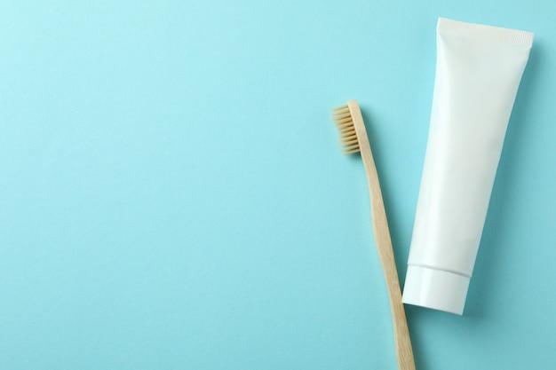 Escova de dentes ecológica e tubo de pasta de dentes em fundo azul