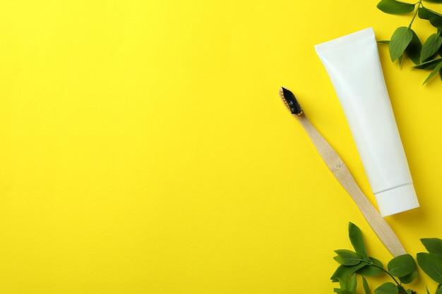 Escova de dentes ecológica, pasta de dentes e ramos em amarelo