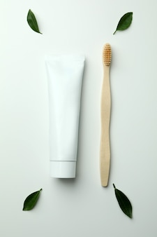 Escova de dentes ecológica, tubo de pasta de dentes e folhas em fundo branco