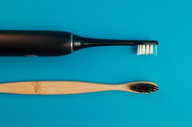 Escova de dentes elétrica e de madeira sobre fundo azul