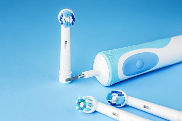 Escova de dentes elétrica moderna e cabeças sobressalentes em fundo azul