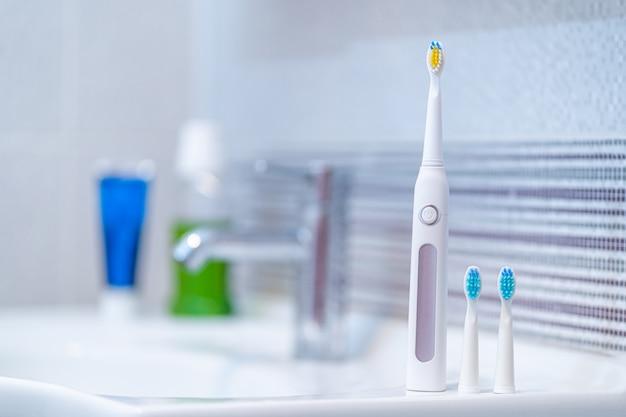 Escova de dentes elétrica ultra-sônica com bicos intercambiáveis no banheiro em casa