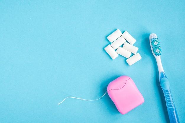 Escova de dentes, fio dental e goma em fundo azul. limpeza e proteção dos dentes