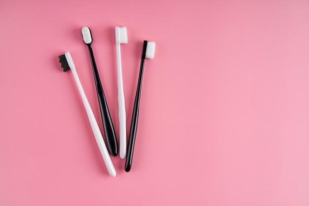 Escova de dentes moderna com cerdas macias. escovas de dentes populares. tendências de higiene. kit de escovas de dente na superfície rosa.