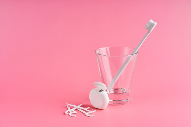 Escova de dentes moderna com cerdas macias. escovas de dentes populares. tendências de higiene. kit de higiene bucal. escovas de dente em vidro, fio dental e palitos em uma superfície rosa.