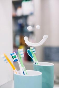 Escova de dentes no copo com sorriso no espelho