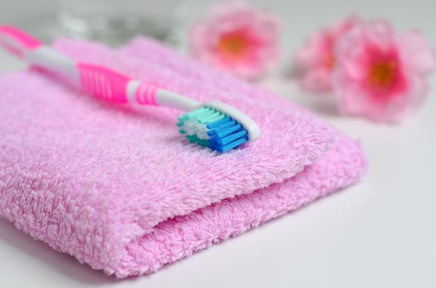 Escova de dentes rosa em uma toalha rosa.