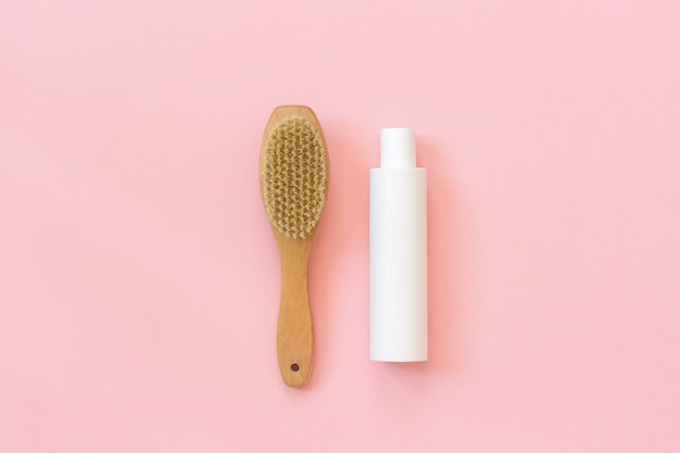 Escova de eco natural e frasco branco de creme para massagem, peeling e cuidados com o corpo.