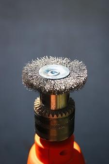 Escova de fixação de aço para furadeira elétrica em fundo cinza para processamento de madeira de limpeza de metal