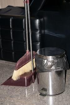 Escova de lixo e pá de lixo lixeira de metal em um salão de beleza