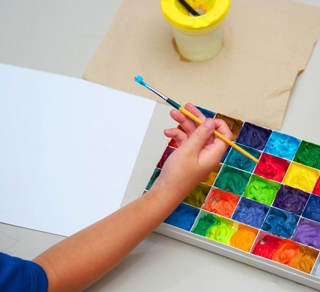 Escova de mão de criança e papel comum com paleta de cores quadrada para obras de arte, vista superior