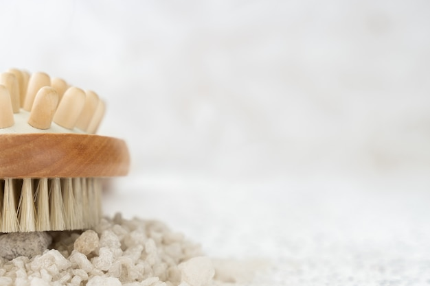 Escova de massagem a seco e sal marinho branco na parede branca