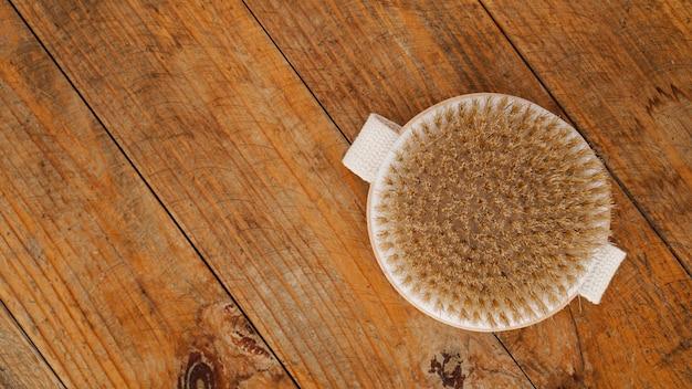 Escova de massagem a seco feita de materiais naturais em um fundo de madeira. minimalismo, copie o espaço.
