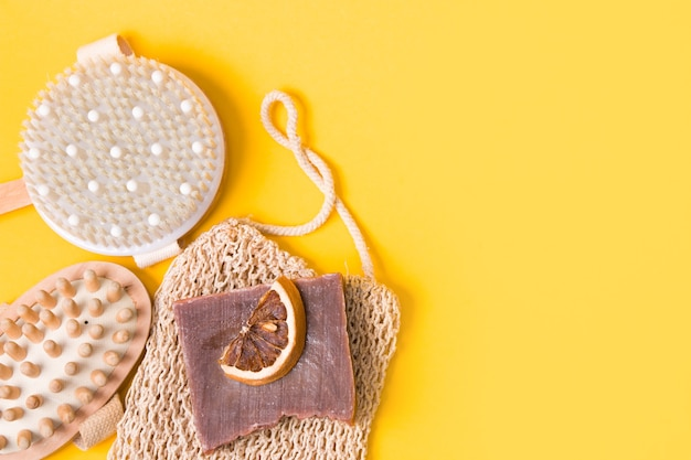 Escova de massagem anticelulite seca, toalha de malha, sabonete de cacau caseiro, fatias de laranja secas e um massageador corporal de madeira em uma superfície amarela