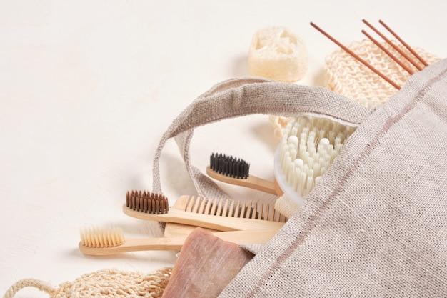 Escova de massagem, palitos de aroma, luffa, escovas de dente de bambu, palitos de aroma e sabonete de cacau caseiro em um saco de pano sobre um fundo de textura bege claro
