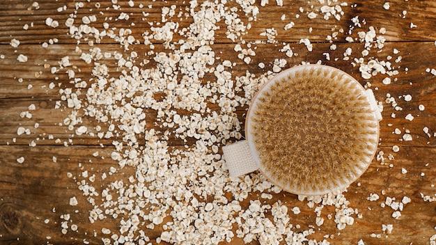Escova de massagem redonda de madeira em um fundo de madeira. farinha de aveia espalhada. o conceito de cosméticos para o corpo a partir de ingredientes naturais
