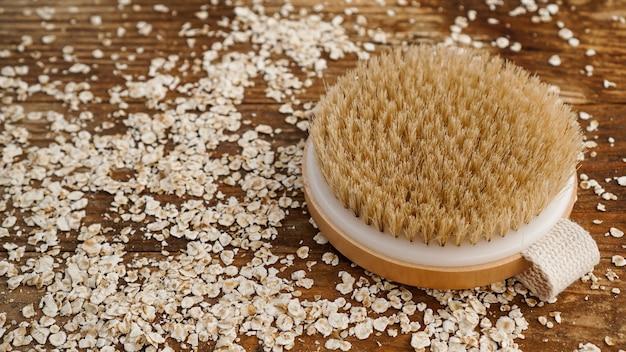 Escova de massagem redonda de madeira sobre uma superfície de madeira. farinha de aveia espalhada. o conceito de cosméticos para o corpo a partir de ingredientes naturais