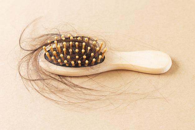 Escova de pente de madeira com cabelo comprido e preto. conceito de problema de queda de cabelo