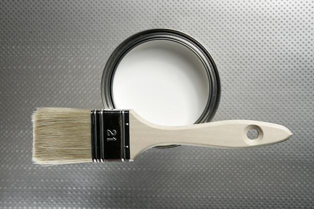Escova de pintor e lata de tinta branca