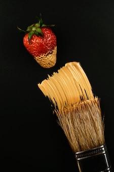 Escova de pintura de cerda de madeira com tinta dourada e morango fresco vermelho no preto.