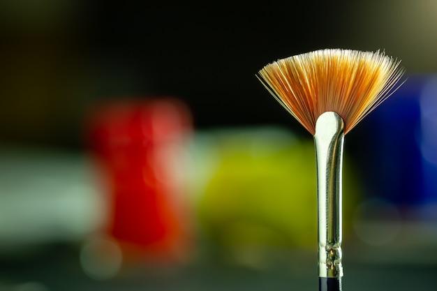 Escova de pintura do artista do close up e fundo do borrão da garrafa da cor de cartaz.