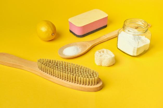 Escova de refrigerante esponja de limão e bucha em fundo amarelo conceito de desperdício zero