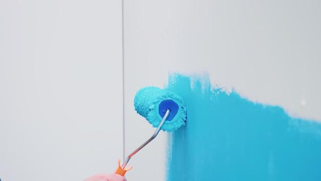 Escova de rolo na parede com tinta azul. redecoração de apartamento e construção de casa durante a reforma e melhoria. reparação e decoração.