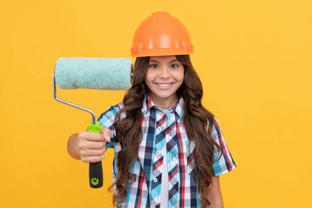 Escova de rolo para decoração. educação infantil. trabalho de renovação. melhorar sua infância. futuro engenheiro. melhoria. fazendo reparos de superfície. garota feliz segurar rolo de pintura. criança no capacete. foco seletivo