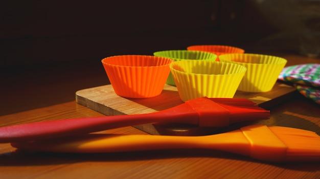 Escova de silicone e forros de cupcake na mesa de madeira. cozinha e conceito de cozinha em fundo de madeira
