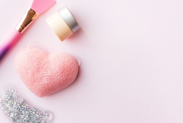Escova de silicone rosa, esponja, hidratante e sob almofada de olho no fundo pastel. conceito de beleza de cuidados da pele.