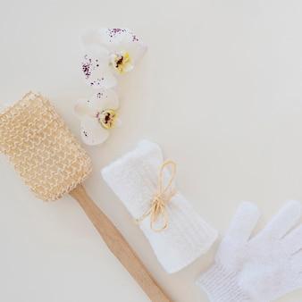 Escova de toalha branca e flor de orquídea para cuidados com a pele