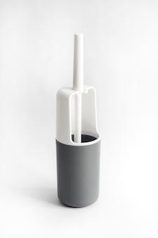 Escova de vaso sanitário de plástico branco e cinza em fundo branco