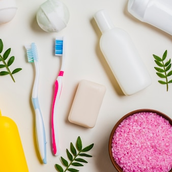 Escova dental; sabonete; bomba de banho; sal rosa e produtos cosméticos em fundo branco