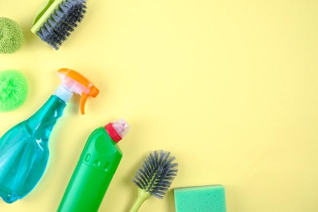 Escova, esfrega e frascos de detergente em fundo amarelo