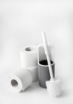 Escova higiênica de plástico branco e cinza e papel higiênico em branco