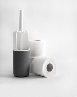 Escova higiênica de plástico branco e cinza e papel higiênico na superfície branca