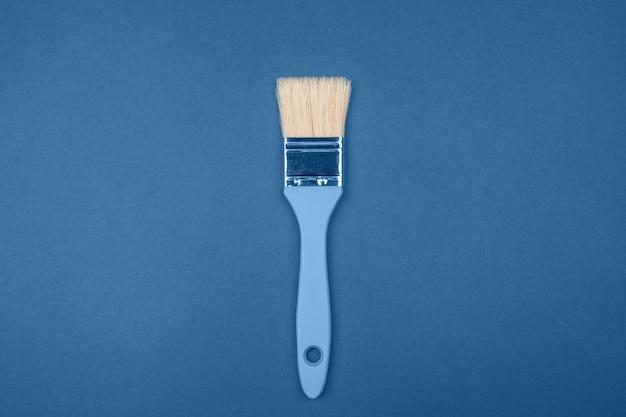 Escova larga com pilha de cerdas naturais sobre fundo azul escuro. conceito de cor principal