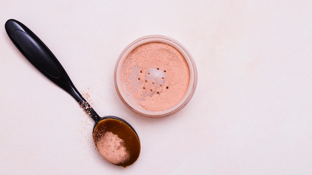 Escova oval preta e pó facial no fundo rosa