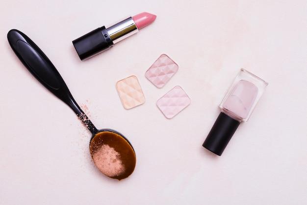 Escova oval preta; pó compacto; batom; verniz de unhas em fundo rosa