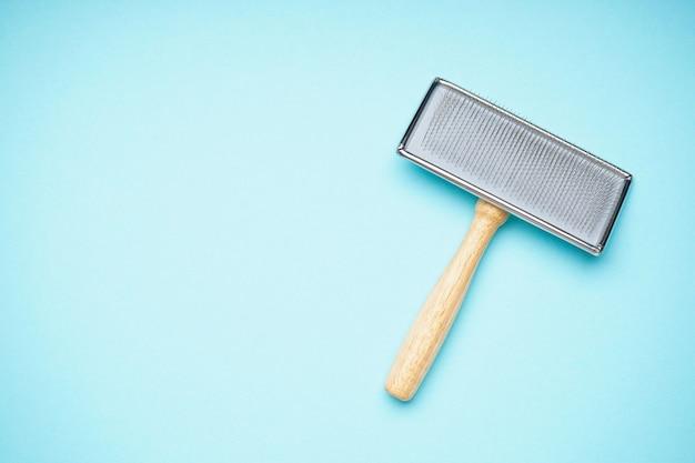 Escova para cães em um fundo azul, espaço para texto. postura plana. escova de aliciamento.