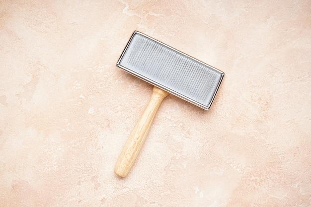 Escova para cães em um fundo bege. escova de aliciamento. postura plana.