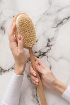 Escova para massagem seca nas mãos de uma menina